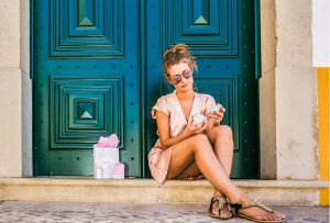 Beautiful girl siting on a stairs and trying Holos products