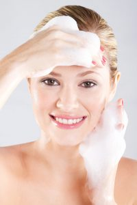 woman washing her face with a foam