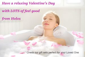 woman having a fragrant bath with flower petals and a few drops of Love Your Skin Body Oil by Holos